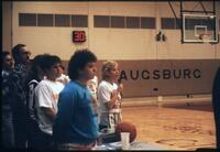 An Augsburg women's basketball team player sings the national anthem before a game, circa 1985.