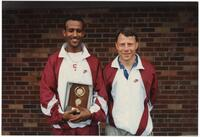 Augsburg men's cross country team coach takes a photo with a runner, circa 1996
