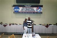 "Augsburg women's track and field team runner takes a photo in front of a sign that reads ""2003 NCAA Division III Men's & Women's Indoor Track & Field Championships, 2003"