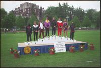Augsburg men's track and field team runner on a championship podium, 2002