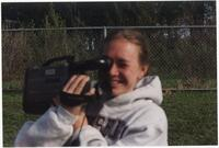 Augsburg women's track and field or cross country team runner holding a video camera, circa 2000