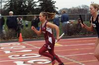 Augsburg women's track and field team runner running during a relay race, circa 2000