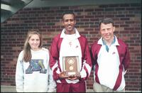 Augsburg men's track and field team runner holding a trophy, 2002