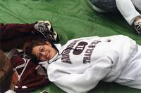 Augsburg women's track and field team runner lying on the ground, circa 2000