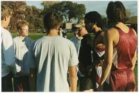 Augsburg men's cross country team coach talks with runners, circa 1996