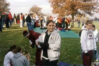 Augsburg women's cross country team runner holding camera, circa 2000