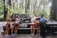 Augsburg women's cross country team runners taking a photo with NYPD police officers, circa 2000