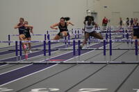 An Augsburg women's track and field team runner hurdling in an indoor race, 2011.