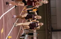 An Augsburg women's track and field team runner running with a baton in a relay race, 2005.