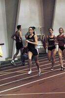 An Augsburg women's track and field team runner running in an indoor race, 2003.
