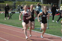 An Augsburg women's track and field team runner running in a race, 2010.
