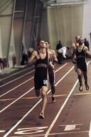 Augsburg men's track and field team runners running in an indoor race, 2003.