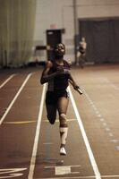 An Augsburg women's track and field team runner running in an indoor relay race, 2003.