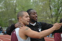 An Augsburg men's track and field team runner with a coach, 2009.