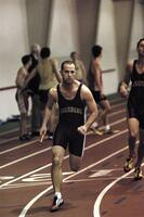 An Augsburg men's track and field team runner runs in a race with a baton, 2003.