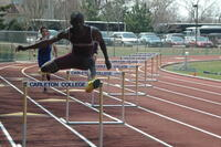 An Augsburg men's track and field team sprinter running in hurdles race at Carleton College, 2009.