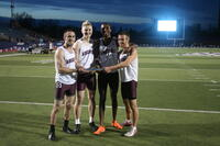 Augsburg men's track and field team runners take photo holding relay baton, circa 2010