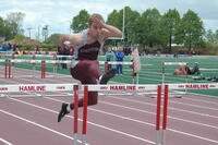 An Augsburg men's track and field team sprinter runs in hurdles race, 2010.