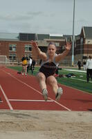 An Augsburg women's track and field team long jumper jumps in an event, 2009.