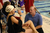 Augsburg women's swimming team member talking with coach, circa 2005