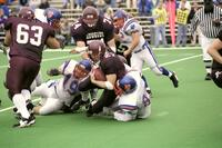 Augsburg men's football player getting tackled while holding the ball, 2001