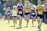 An Augsburg women's cross country team runner running in a race at the 2013 MIAC Championships, 2013.