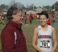 An Augsburg women's cross country team runner takes a picture with her coach at the Division III Central Region Championships, 2011.