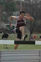 An Augsburg men's track and field team sprinter running in hurdles race, 2009.