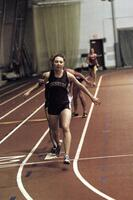 An Augsburg women's track and field team runner receives a baton from a team runner in a race, 2003
