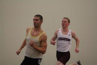 An Augsburg men's track and field team runner running in an indoor race, 2011.