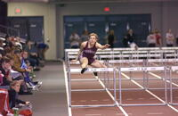 An Augsburg women's track and field team runner runs in a hurdling event, 2005.