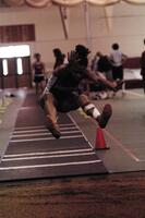 An Augsburg women's track and field team long jumper jumps in an event, 2003.