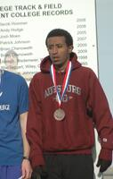 An Augsburg men's cross country team runner receives a bronze medal after a race, 2011.