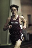 An Augsburg men's track and field team runner running in an indoor race, 2003.