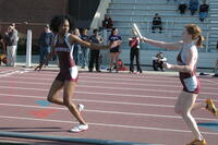 An Augsburg women's track and field team runner receives a baton from a teammate in a race, 2010.