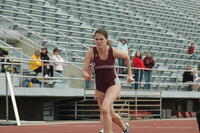 An Augsburg women's track and field team sprinter running in a hurdles race at Macalester College, 2009.
