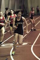 An Augsburg women's track and field team runner runs in a race with a baton, 2003.