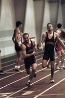 An Augsburg men's track and field team runner passes a baton to a teammate in a race, 2003.