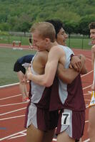 An Augsburg men's track and field team runner hugs a teammate after a race, 2010.