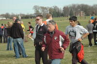 An Augsburg men's cross country team coach jogging during the Division III Central Region Championships, 2011.
