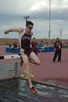 An Augsburg men's track and field team runner running in a hurdles race, 2009.