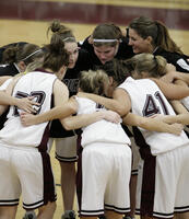 Augsburg women's basketball players in a huddle, circa 2005