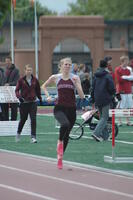 An Augsburg women's track and field team runner running in relay race with a baton, 2010.