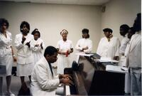 A Black choir singing around a piano, circa 1988