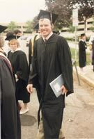 A graduate smiling at the camera, 1989