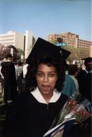 A Black graduate smiles at the camera, 1989