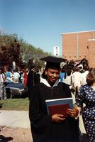 A Black graduate smiling at the camera, circa 1988