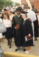 A Black graduate taking a photograph with an unidentified person, 1989
