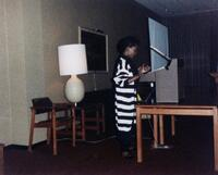 A Black person speaking to a room, 1990