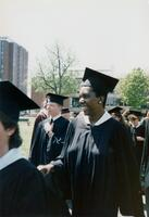 A Black graduate smiling in their cap and gown, 1990